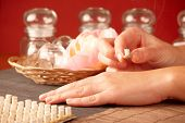 TCM Traditional Chinese Medicine. Hand applying mini moxa stick therapy, natural herbs in glass jars in background poster