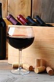 A glass of red wine in front of a wooden case of wine bottles on a rustic wood background. Vertical