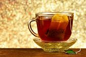 Tea In A Bag In A Cup On A Saucer, Background Rainbow Lights Bokeh. Helpful Tea Is Popular Refreshin poster
