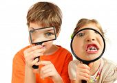 Brother and sister looking through magnifying glasses isolated on white background