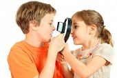 Brother and sister look at each other through magnifying glasses isolated on white background