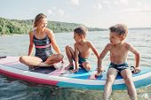 Caucasian Woman Parent Sitting On Paddle Sup Surfboard In Water With Kids Children. Modern Outdoor F poster