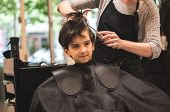Hairdressers Hands Making Hairstyle To Child Little Boy In The Barber Shop Hair Cut Professional - L poster