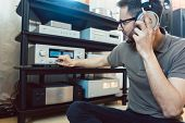 Man turning up the volume on home Hi-Fi stereo for louder music poster
