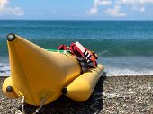 Inflatable Banana By The Sea. Inflatable Boat For Speed Swimming In The Sea. On The Shore Is A Yello poster