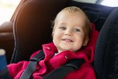 Cute Caucasian Toodler Boy Sitting In Child Safety Seat In Car During Road Trip. Adorable Baby Smili poster