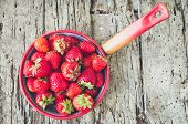 Background From Freshly Harvested Strawberries. Metal Colander Filled With Succulent Juicy Fresh Rip poster
