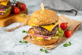 A Set Of Homemade Delicious Burgers Of Beef, Bacon, Cheese, Lettuce And Tomatoes On A Light Concrete poster