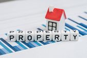 Cube Block With Alphabets Building The Word Property With Small House On Yearly Chart And Graph Repo poster