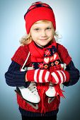 Portrait of a cute little girl in warm hat and sweater posing with figure skates.