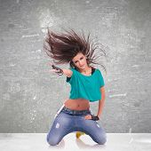 headbanging woman dancer standing onher knees on gray background
