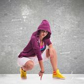 young hip hop woman dancer wearing a hoodie, posing crouched and touching the floor