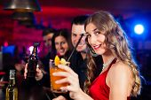 Group of party people with cocktails in a bar or club having fun; one woman is looking into the came