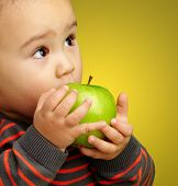 Portrait Of Baby Boy Eating Green Apple against a yellow background