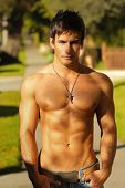 A young topless fit man standing outside