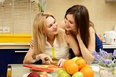 Mother with her daughter teenager peel and cut vegetables together in kitchen at home