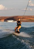 Brunette Woman Wakboarding At Sunset