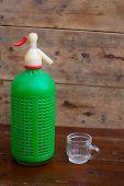 alte Limo-Flasche mit kleinen Tasse im hölzernen Hintergrund