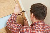 Male handyman carpenter at interior wood door lock installation