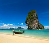 Thailand tropical vacation concept background - Long tail boat on tropical beach with limestone rock