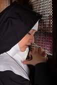 Praying nun kneeling in a traditional confession booth