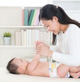 Asian mother playing with baby girl at home.