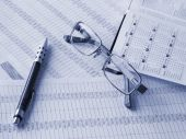 Daily Book, Pen And Glasses On Financial Documents.