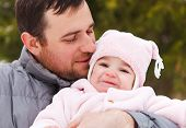 stock photo of father time  - Happy smiling father with one year old baby girl outdoors. Winter time