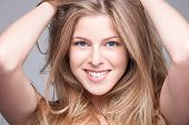 close up of a smiling natural blonde blue eyed  young beauty portrait woman studio shot