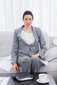 Outraged businesswoman sitting on sofa looking at camera at office