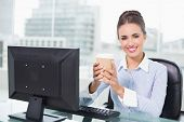 Smiling brunette businesswoman holding disposable cup in bright office