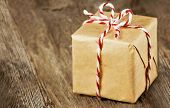 stock photo of tied  - Christmas style rustic brown paper package tied up with strings - JPG