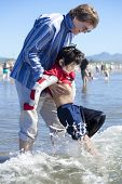 Father Helping Disabled Son Walk In The Ocean Waves On Beach