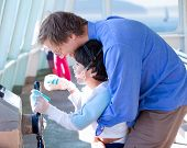 pic of babysitting  - Father holding up disabled son helping him to play with steering wheel on ferry boat deck - JPG