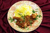 Homemade butter chicken masala with yellow and white rice, garnished with chopped coriander leaves.