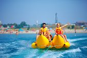 Happy People Having Fun On Banana Boat