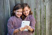 twin girls fancy dressed up pretending be siamese with dad shirt playing with tablet pc