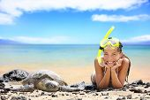 Beach travel woman on Hawaii with sea sea turtle. Snorkeling girl on vacation wearing snorkel smiling happy enjoying blue sky and sun lying next to Hawaiian sea turtles on Big Island, Hawaii, USA.