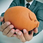a man wearing a suit holding a piggy bank in his hands