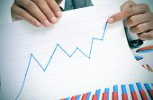 man wearing a suit sitting in a table showing a graph of economic growth