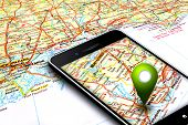stock photo of gps navigation  - mobile phone with gps laying on map background - JPG