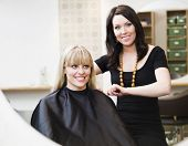 Hairdresser in action with blond customer