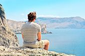 Young Man Relaxing On Rocky Cliff Sitting And Looking On Sea And Mountains Summer Time Freedom Conce