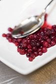 Lingonberries and a spoon on white plate