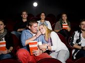 Young Couple at the Movie Theater eating popcorn