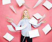 stock photo of baseboard  - Businesswoman with flying papers on pink background - JPG