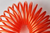 Orange red spiral plastic air hose used for pneumatic tools.