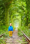 Smiling Kid Walking The Rails In Green Tunnel