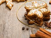 image of ginger bread  - Snowflake shaped Gingerbread cookies stacked and tied with a gold bow - JPG