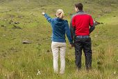 Couple holding hands with woman pointing on a walk in the countryside